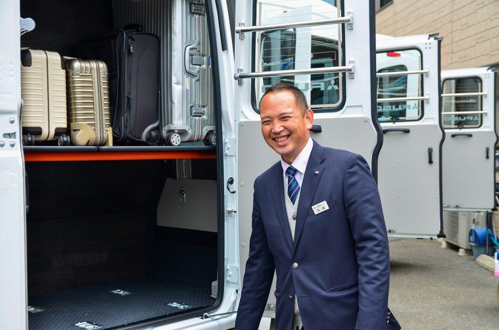 トランク付きマイクロバスを案内する笑顔の運転手