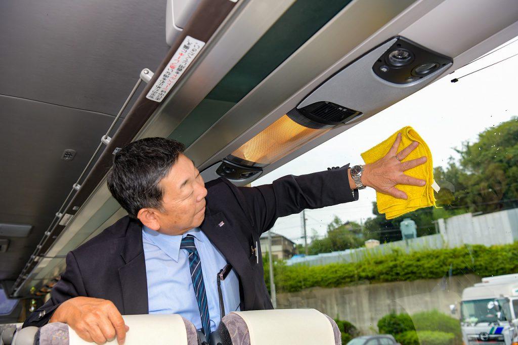 バスの窓をピカピカにする運転手