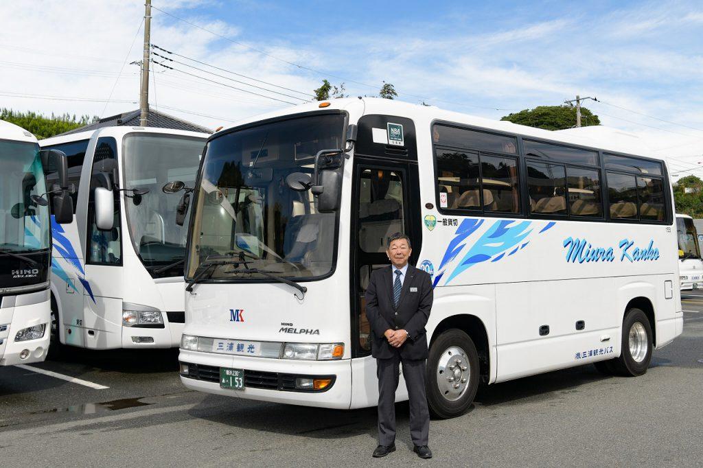 小型観光バスと笑顔のベテラン運転手